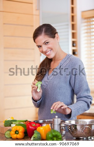 Smiling young woman preparing vegetable stew in the kitchen