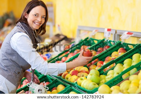 Smiling young woman purchasing fresh apples from a grocery display in a supermarket turning to smile at the camera - stock photo