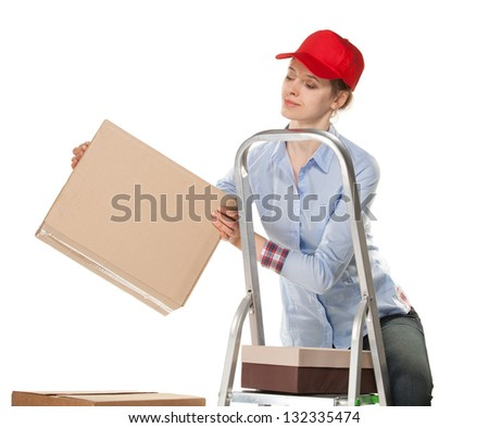 Smiling young woman puts a box on white background - stock photo
