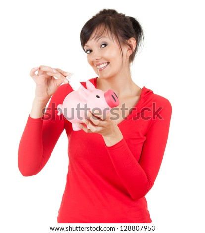 smiling young woman putting money into pink piggy bank, white background