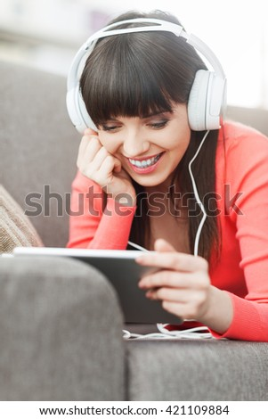 Smiling young woman relaxing at home on the couch, she is wearing headphones, using a digital tablet and watching a movie online