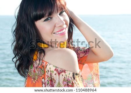 Smiling young woman relaxing on the shore, horizontal shot - stock photo