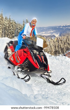 Smiling young woman riding a snowmobile against winter landscape - stock photo