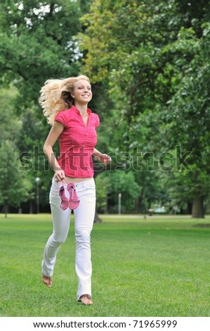Smiling young woman running barefoot on grass in park and holding her shoes in hand - stock photo