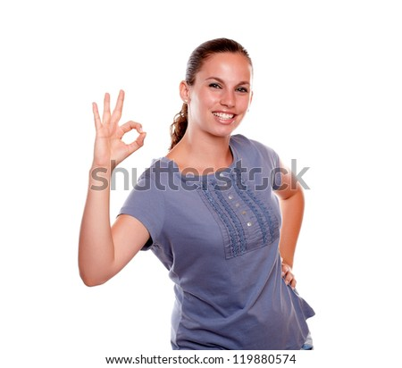 Smiling young woman saying great job looking at you against white background - stock photo
