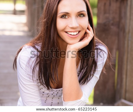 Smiling young woman sits on wooden porch.