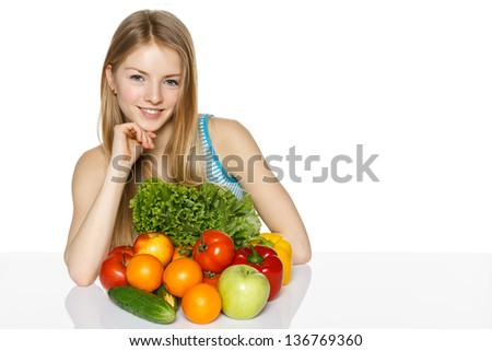 Smiling young woman sitting at the table with vegetable on it against white background