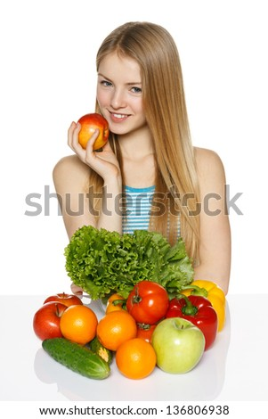Smiling young woman sitting at the table with vegetable on it holding apple in her hand, against white background