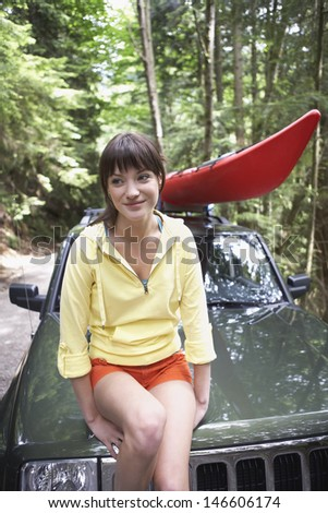 Smiling young woman sitting on car bonnet in the forest - stock photo