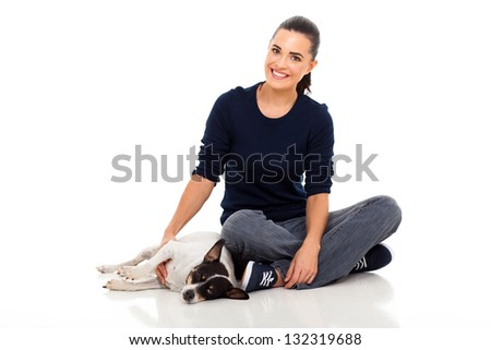smiling young woman sitting on floor next to her dog isolated on white