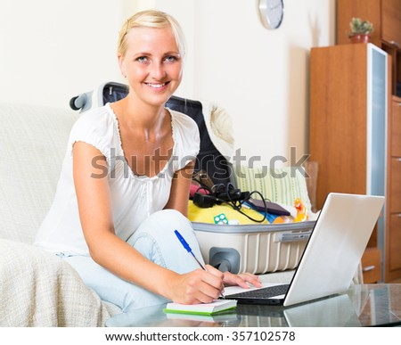 Smiling young woman sitting on sofa at home with laptop, notes and packed baggage