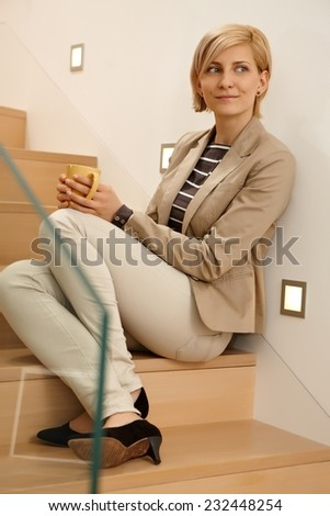 Smiling young woman sitting on stairs, drinking tea, looking away. Full size. - stock photo