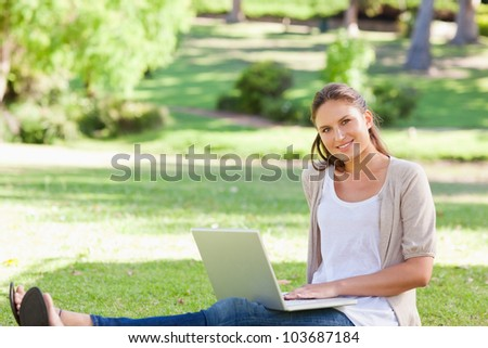 Smiling young woman sitting on the grass with her laptop