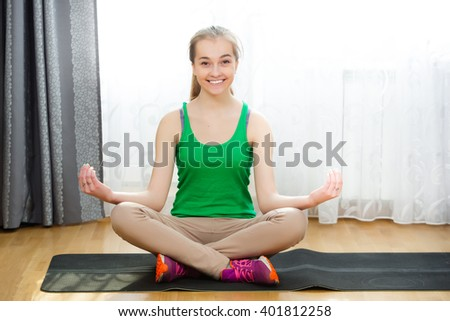 Smiling young woman sitting on yoga mat at home - stock photo