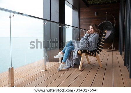Smiling young woman sitting wrapped in knitted coverlet on the glass balcony - stock photo