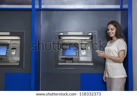 Smiling young woman standing in front of ATM and looking at her phone