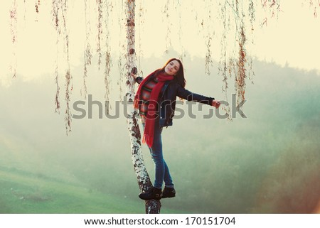 smiling young woman standing on tree in park autumn day retro colors - stock photo