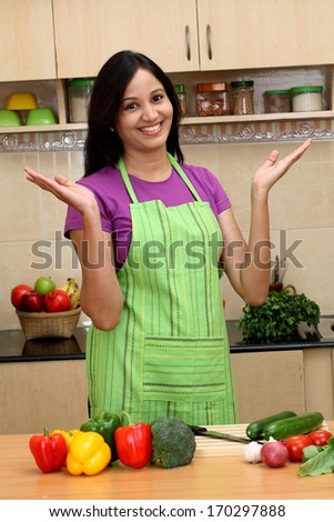 Smiling young woman standing with open palms in kitchen - stock photo