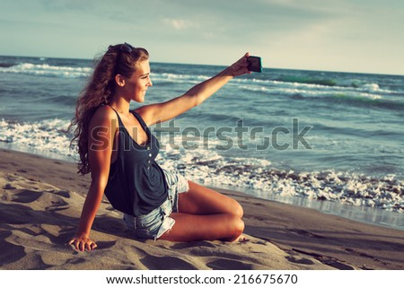 smiling young woman take a selfie photo at sandy beach by the sea at sunset - stock photo