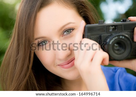 Smiling young woman taking photographs with a pocket camera.