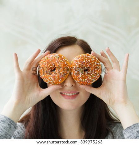 Smiling young woman taking sweets donuts on eyes.