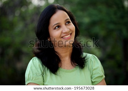 Smiling young woman thinking at outdoors - stock photo