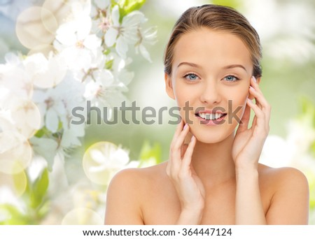 smiling young woman touching her face - stock photo