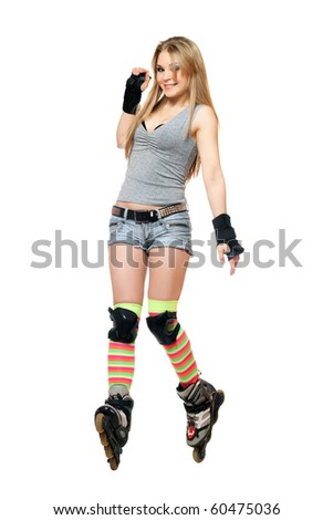 Smiling young woman tries to keep his balance on roller skates - stock photo