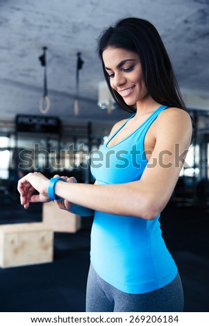 Smiling young woman using activity tracker at gym - stock photo