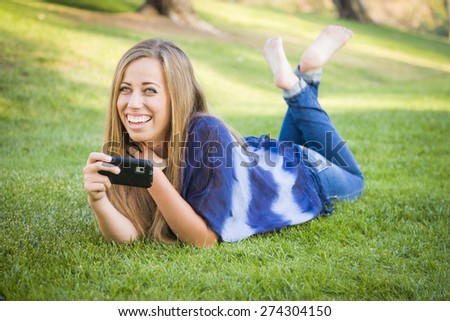 Smiling Young Woman Using Cell Phone Outdoors at the Park. - stock photo