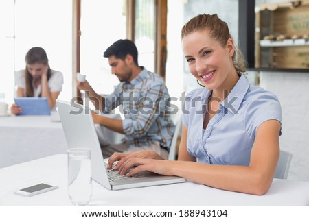 Smiling young woman using laptop in the coffee shop