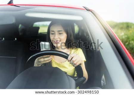 Smiling young woman using mobile phone at the car. - stock photo