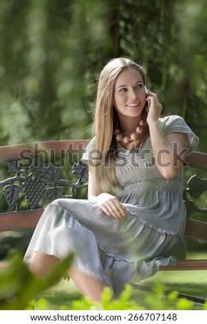 Smiling young woman using mobile phone on park bench - stock photo