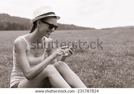 Smiling young woman using mobile smart phone - stock photo