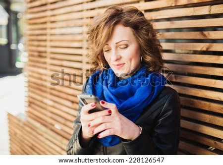 Smiling young woman using mobile smartphone on the street