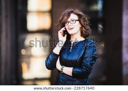 Smiling young woman using mobile smartphone on the street - stock photo