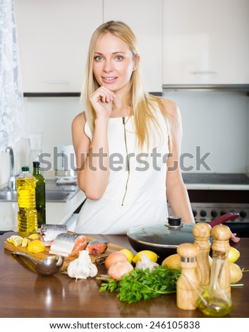 Smiling young woman using new slow-cooker in kitchen - stock photo