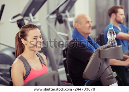 Smiling Young Woman Using Recumbent Exercise Bike in Busy Gym - stock photo