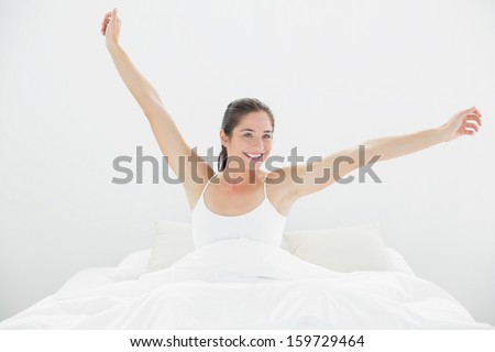 Smiling young woman waking up in bed and stretching her arms - stock photo