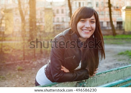 Smiling young woman walking on the spring park in sun rays, leaning to bench