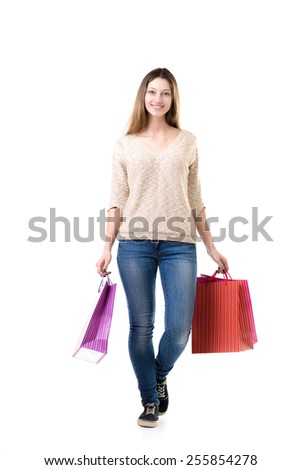 Smiling young woman walking with heap of shopping bags, happy with her purchases - stock photo