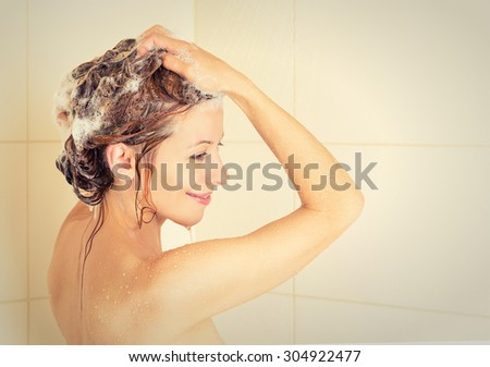 Smiling young woman washing head with shampoo in a shower