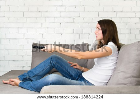 Smiling young woman watching TV on a sofa  - stock photo