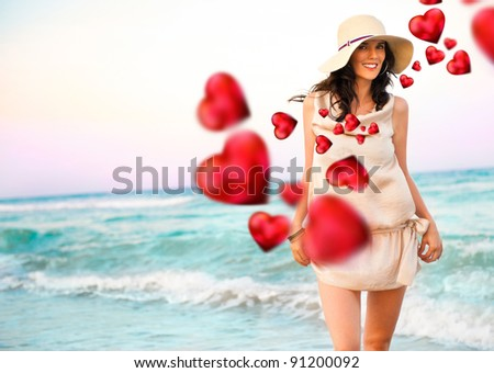 Smiling young woman wearing a straw hat and having fun at the beach. Beautiful red hearts are flying around her - stock photo
