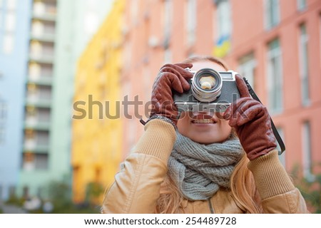 Smiling young woman wearing gloves making photo with retro camera at the city. Focus on the lens. - stock photo