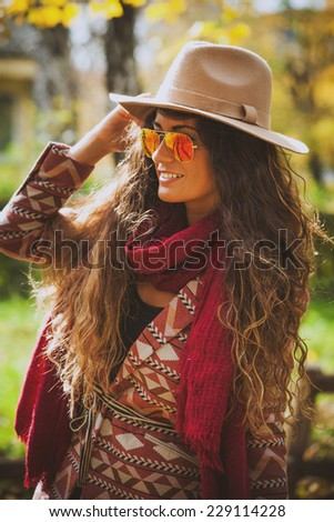 smiling young woman wearing hat, sunglasses, red scarf and jacket, outdoor autumn fashion portrait in sunny park - stock photo
