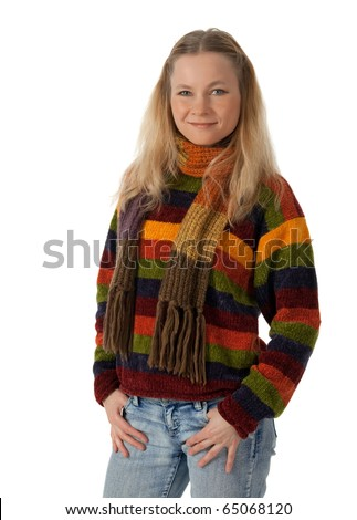 Smiling young woman wearing striped sweater and scarf, holding hands in pockets. - stock photo