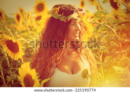 smiling young woman wearing white dress and wreath of flowers enjoy in  sunflower field , retro colors