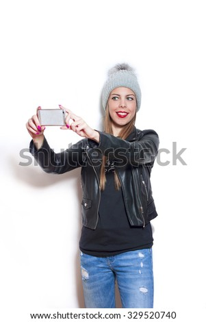 smiling young woman wearing wool cap,  blue jeans and leather jacket  take selfie with smartphone - stock photo