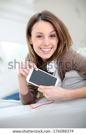 Smiling young woman websurfing with smartphone - stock photo